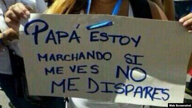 Una estudiante muestra una pancarta en la que le pide a su papá (un militar) que no le dispare.