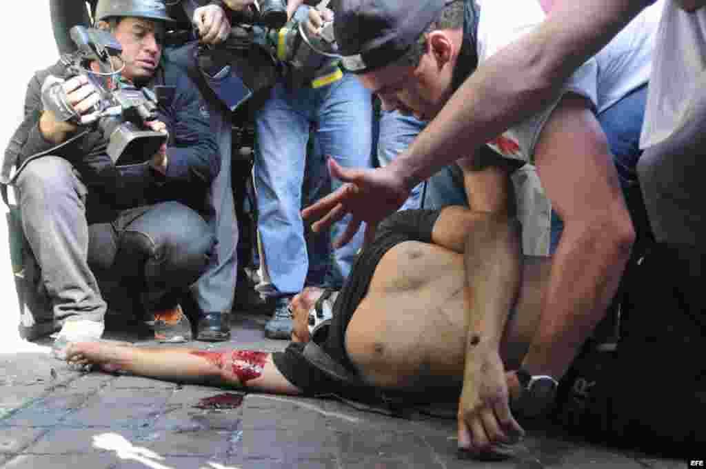Un hombre yace en el piso luego de ser herido de bala durante una manifestación en Caracas.
