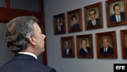 Juan Manuel Santos mira las imágenes de los magistrados de la Corte Suprema de Justica que murieron durante la toma del Palacio de Justicia. EFE