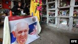 Una mujer prepara un altar en una mesa con una imagen del papa Francisco hoy, jueves 9 de julio de 2015, en la sede que fuera del supermercado Ycuá Bolaños en Asunción (Paraguay).