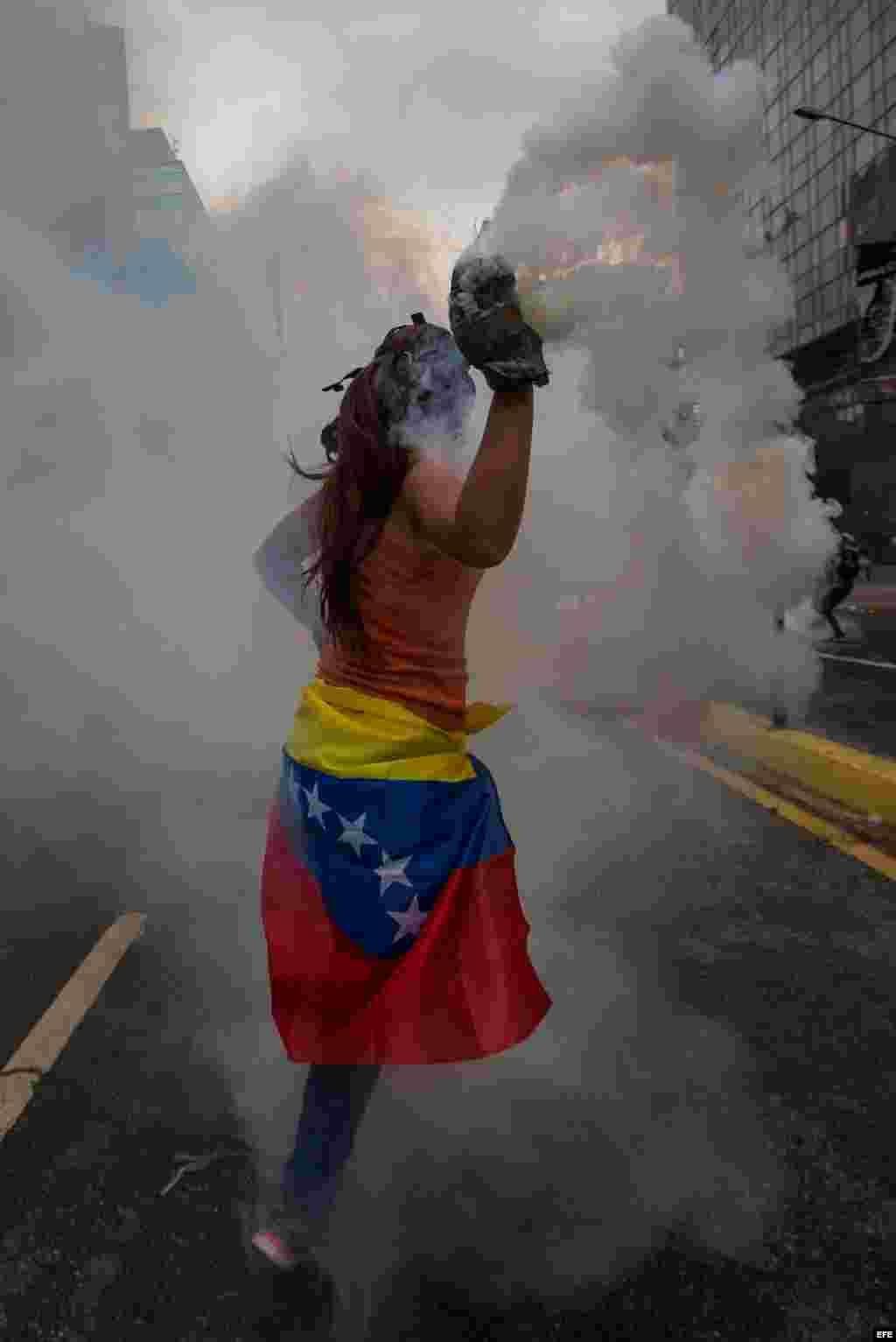 Una mujer destaca vestida con la bandera nacional entre los manifestantes que se enfrentaron con agentes de la Guardia Nacional Bolivariana el jueves 20 de abril de 2017, en Caracas (Venezuela).
