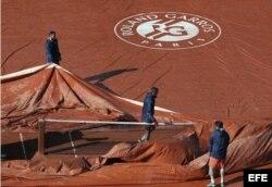 El personal prepara la pista Philippe Chatrier de Roland Garros.