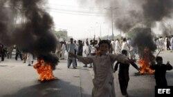 KHI06 LARKANA (PAKISTÁN) 21/09/2012.- Paquistaníes incendian neumáticos durante una manifestación contra la polémica película sobre Mahoma, en Pakistán, hoy, viernes 21 de septiembre de 2012. Las embajadas de Europa y EEUU han extremado la seguridad por t
