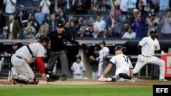 Brett Gardner (d) de Yanquis se desliza frente al receptor Sandy León (i) de Medias Rojas el miércoles 9 de mayo de 2018, en un juego de la MLB entre Medias Rojas de Boston y Yanquis de Nueva York en el estadio de Yanquis en Nueva York (EE.UU.). EFE/JASON