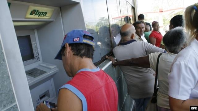 Un residente local extrae dinero de un cajero automático mientras otros hacen fila.