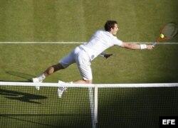 El tenista británico Andy Murray devuelve la bola durante el partido de cuartos de final del torneo de Wimbledon que disputó contra el español Fernando Verdasco.