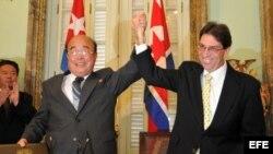 El canciller cubano, Bruno Rodríguez (d), toma la mano del ministro de Relaciones Exteriores de Corea del Norte, Pak Ui Chun (i).