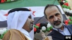 El presidente de la la opositora Coalición Nacional Siria (CNFROS), Ahmad Mouaz Al-Khati (d) escucha al ministro de Asuntos Exteriores de Catar, Khalid bin Mohammed Al-Attiyah (i) durante el acto de entrega de la la Embajada siria en Doha .