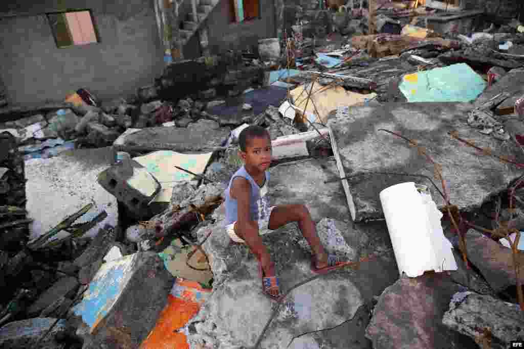 Un niño sentado en los escombros hoy, viernes 7 de octubre de 2016, tras el paso hace tres días del huracán Matthew en Baracoa (Cuba).EFE/Alejandro Ernesto