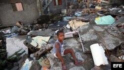 Un niño sentado en los escombros tras el paso del huracán Matthew en Baracoa. EFE/Alejandro Ernesto