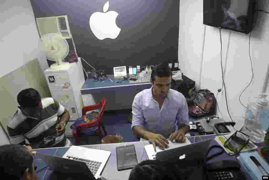 Un joven cubano atiende en su negocio de reparaciones de Iphones, en La Habana.