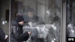 La policía forense inspecciona los agujeros de bala en la puerta del Café Krudttoenden en Copenhague.