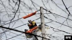 Un trabajador intenta restaurar el servicio eléctrico en Staten Island, Nueva York.