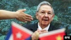 Raúl Castro durante un viaje a China, mientras ondea banderitas de Cuba y el país asiático.