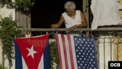 Un hombre coloca las banderas de EE.UU. y Cuba.