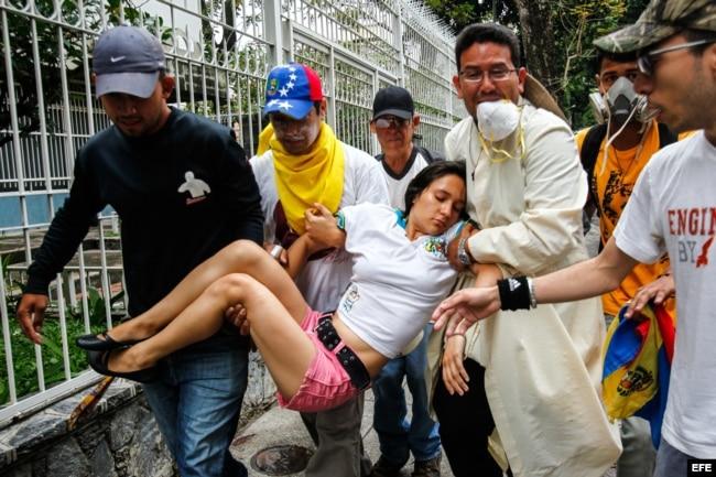 Un grupo de hombres carga a una mujer desmayada a causa de los gases lacrimógenos durante una confrontación de opositores con la Policía Nacional Bolivariana en Caracas.