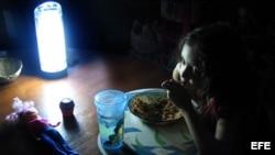 Niña come alumbrada por una lámpara de baterías durante un apagón en Cuba.