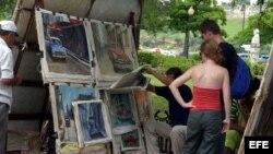 Turistas observan pinturas expuestas en una feria de artesanos de La Habana Vieja.