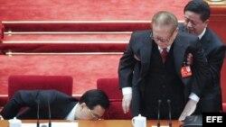 El presidente de China, Hu Jintao (i), guarda sus documentos en un cajón mientras un asistente ayuda a levantarse al expresidente Jiang Zemin tras la clausura del XVIII Congreso del PCCh.