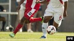 Kahlil Velásquez (i) de Belice ante Yoel Colome (d) de Cuba durante un partido