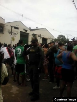 La policía antimotín rodea el almacén donde se refugian los cubanos.
