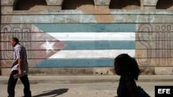 Varias personas caminan junto a una bandera pintada sobre un muro.