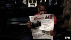 """Un hombre lee el diario oficial """"Granma"""" con información sobre el presidente de EEUU, Barack Obama, en una calle de La Habana."""
