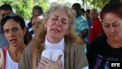 Inés González (c), madre de uno de los fallecidos en el desastre aéreo que cobró la vida de 108 ocupantes del avión accidentado ayer en la Habana, llora al salir del instituto de Medicina Legal donde se identifica a las víctimas.