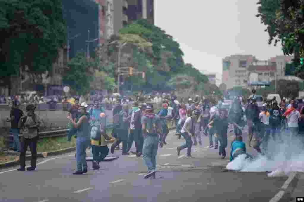 Manifestantes protestan en medio de gases lacrimógenos lanzados por miembros de la Policía Nacional Bolivariana (PNB) hoy, 18 de mayo de 2016, en la ciudad de Caracas (Venezuela).