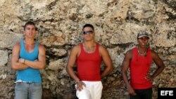 Tres jóvenes cubanos posan en una céntrica calle de La Habana (Cuba).