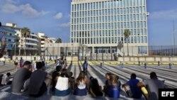 Periodistas y curiosos aguardan frente a la Embajada de Estados Unidos en Cuba en La Habana
