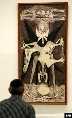 """Un hombre observa la obra """"Anunciación (Natividad)"""", de Lam, en el Museo Reina Sofía."""