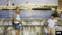 """Dos niños delante de una replica del """"Malecon"""" de la Habana durante el evento """"Cuba Nostalgia""""."""