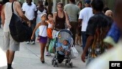 Una mujer camina con sus hijos por una céntrica calle de La Habana (Cuba).