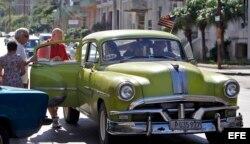 Varios turistas suben a un auto con la bandera de Estados Unidos