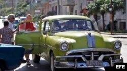 Varios turistas suben a un auto con la bandera de Estados Unidos en La Habana. (Archivo)