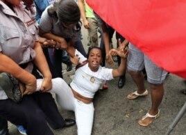 Yaquelin Boni, de las Damas de Blanco es detenida, entre hostigamiento e insultos de sectores oficialistas el 10 de diciembre de 2015, en La Habana (Cuba).