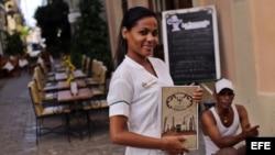 Una mesera posa mientras espera la llegada de clientes en un restaurante privado en La Habana.