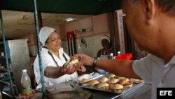 Una mujer vende pan con cerdo en un puesto callejero en La Habana (Cuba).