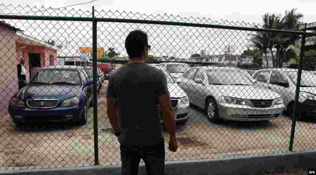 Cubanos observan autos en venta.