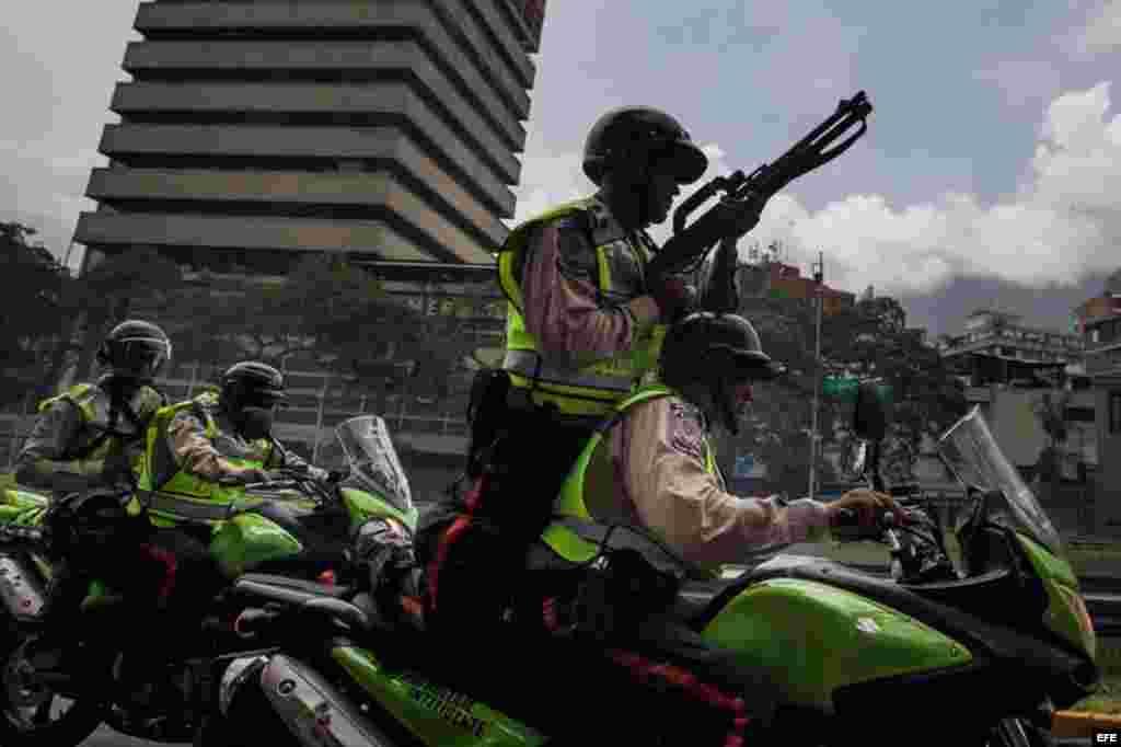 Miembros de la Policía Nacional Bolivariana (PNB) patrullan en motocicletas fuertemente armados frente a la manifestación.