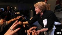 La candidata presidencial por la Coalición Nueva Mayoría ( Partido Socialista PS, Partido Por La Democracia PPD y el Partido Comunista), Michelle Bachelet (d), festeja con sus seguidores tras su triunfo en las primeras elecciones primarias presidenciales