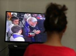 Una mujer observa el Noticiero Nacional de la Televisión cubana que muestra imágenes de Fidel Castro ejerciendo su derecho al voto.