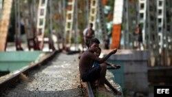 Jóvenes departen al lado de una vía férrea en Matanzas (Cuba).