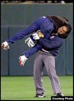 El árbitro Luis César Valdés aplica artes marciales para derribar a Diego Tintorero en el juego Cuba-Orioles, mayo de 1999.