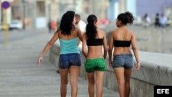 Tres mujeres caminan por el malecón.
