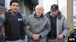 Fotografía de archivo del 17 de julio de 2012 en la que se observa al exdictador argentino Jorge Rafael Videla (c) escoltado por la policía en la localidad de San Martín, provincia de Buenos Aires (Argentina).