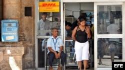 Un empleado estatal custodia la puerta de una oficina de correos en La Habana.