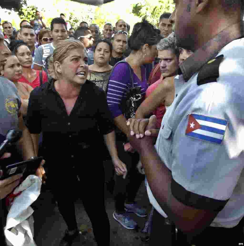 Una mujer discute con un uniformado mientras un grupo de cubanos protesta frente a la embajada de Ecuador en Cuba.