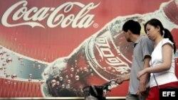 Foto de archivo del 14 de junio de 2005 que muestra a una pareja caminando frente a una publicidad de Coca-Cola en PeKín, China.